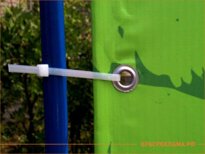Зеленый банер закреплен к синей штанге